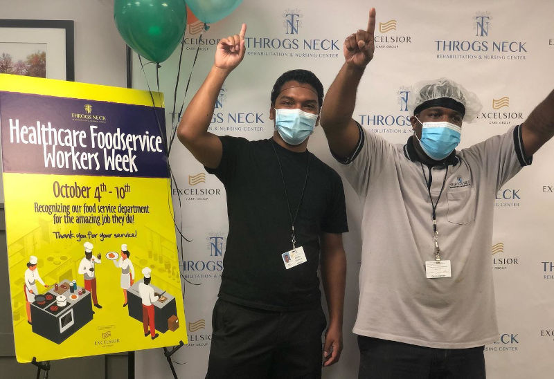 Two employees holding up 1 finger